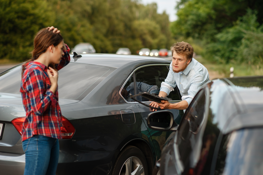 Male and female drivers on road, car accident