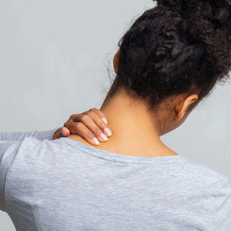 Black woman rubbing her neck, rear view